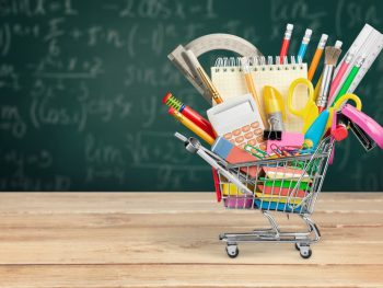 A shopping cart filled with school supplies set against a chalkboard background.