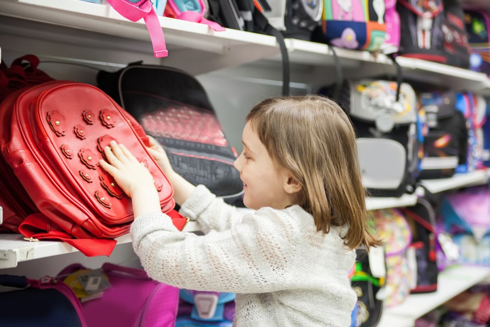 A young girl chooses a backpack for back-to-school.