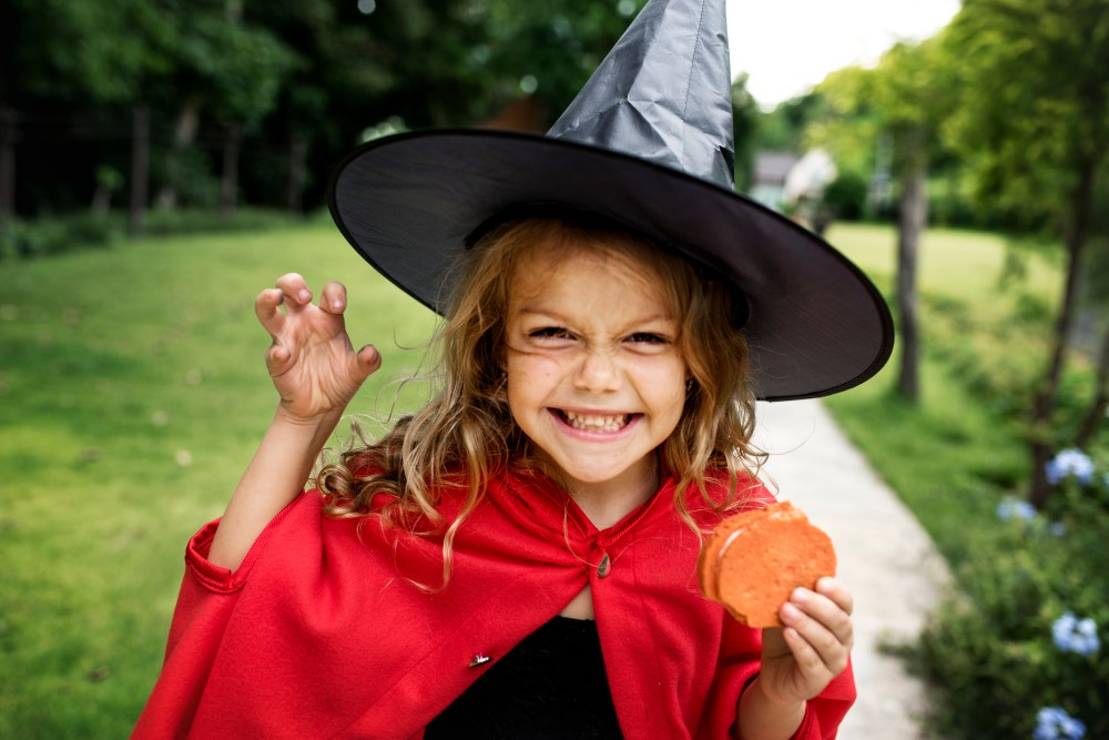 A young girl dressed for Halloween as a witch and eating a pumpkin cookie.
