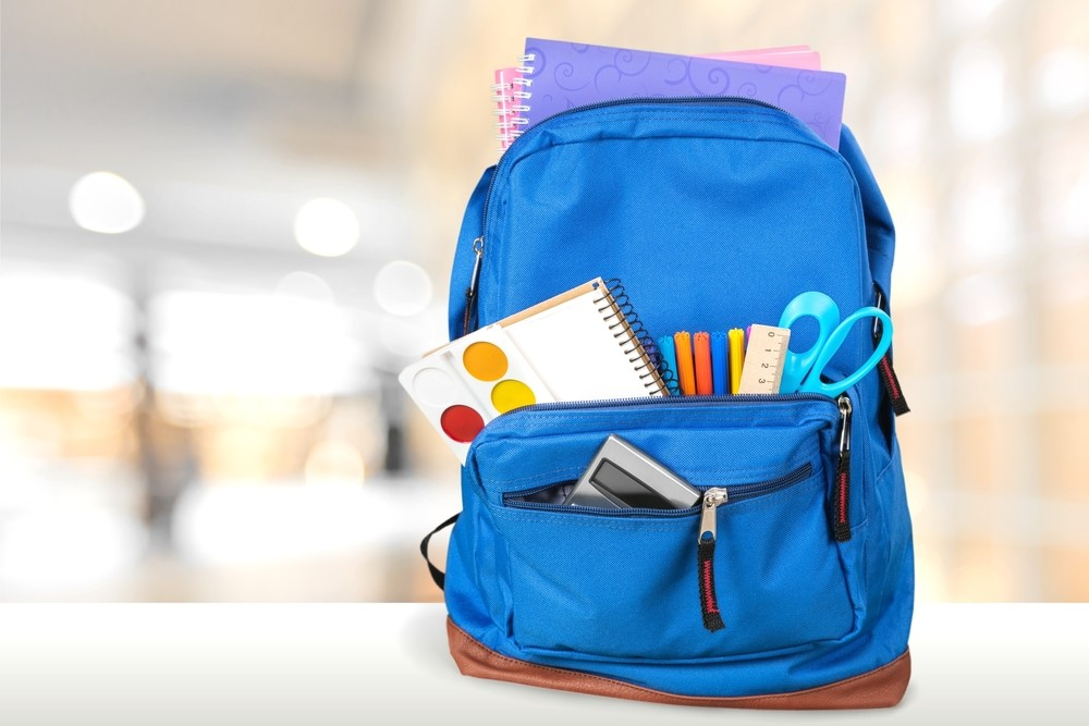 A blue backpack is filled with school supplies.