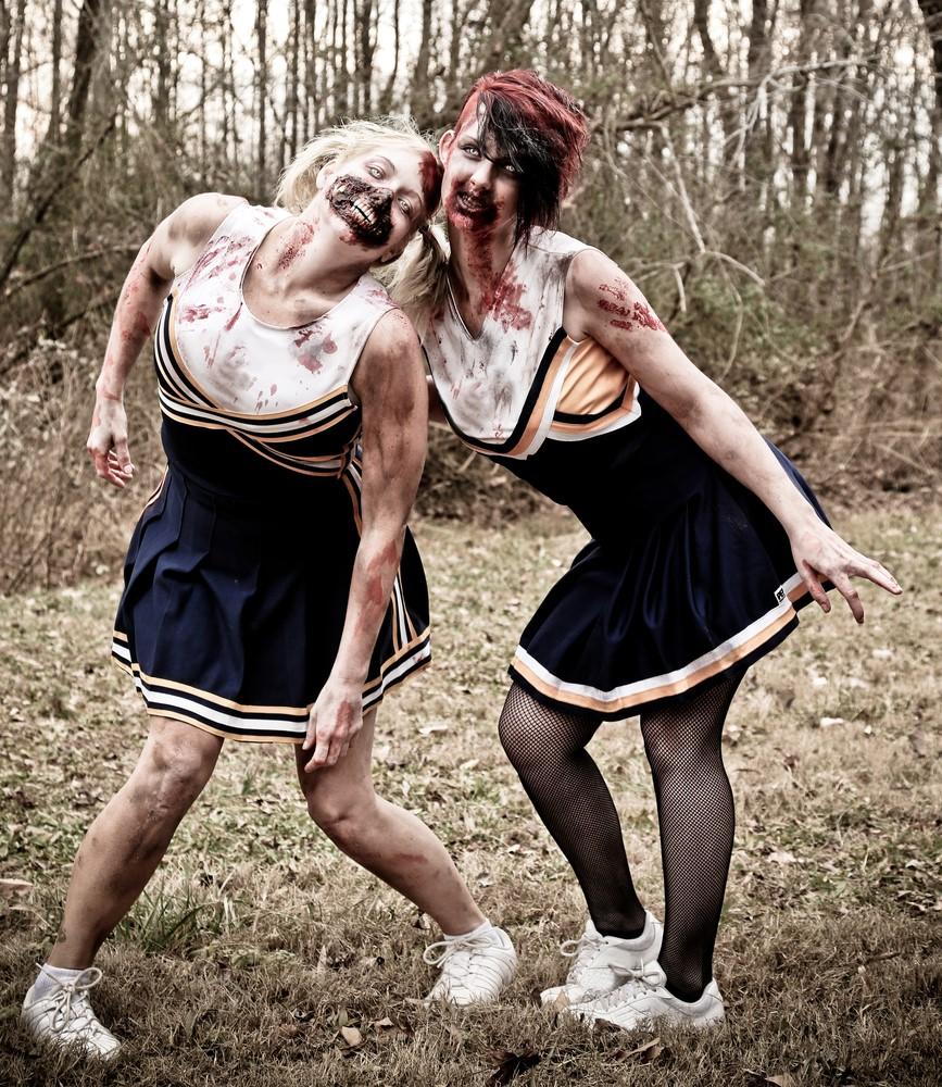 Two teenagers dressed up for Halloween as zombie cheerleaders.