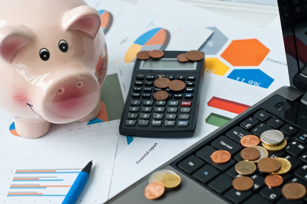 A piggy bank, calculator and coins set next to graphs to illustrate budgeting.