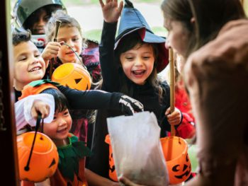 A group of kids trick or treating and receiving candy from a neighbor.