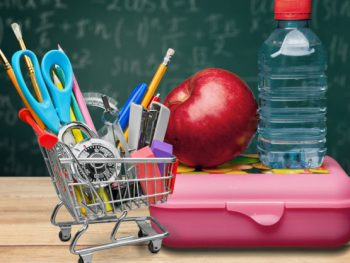 A shopping cart filled with school supplies next to an apple and water bottle on top of a lunch box.