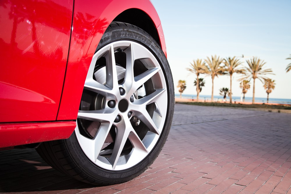 A red car pulling up to the beach with cool rims