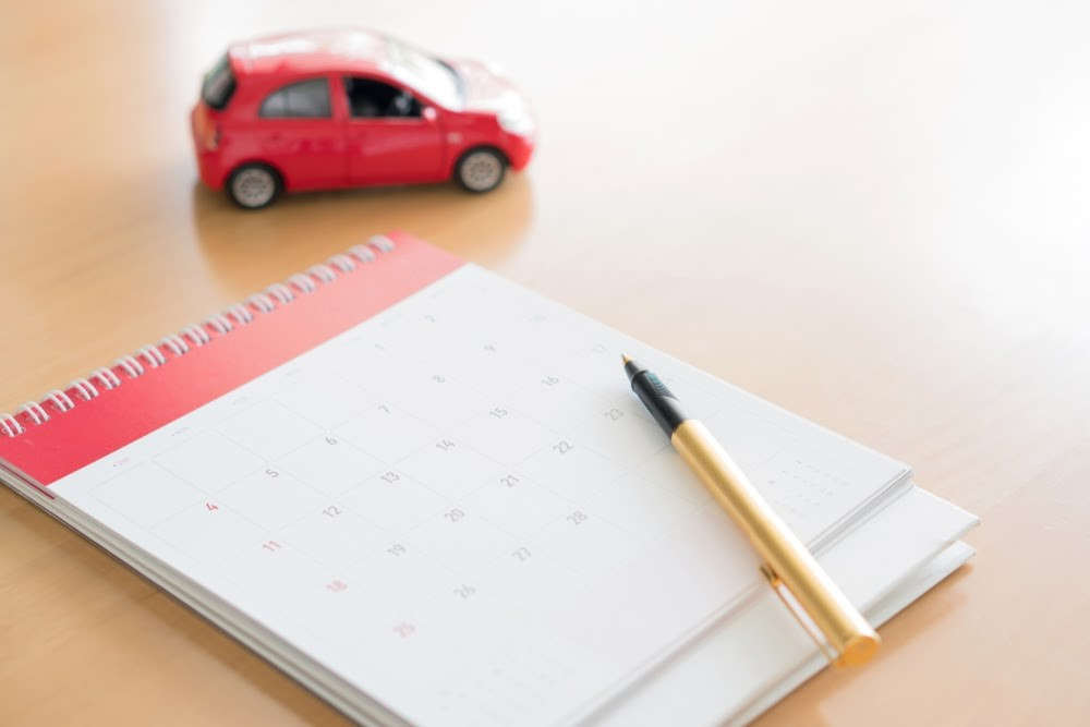 A Little Red Toy Car on a Table with a Calendar