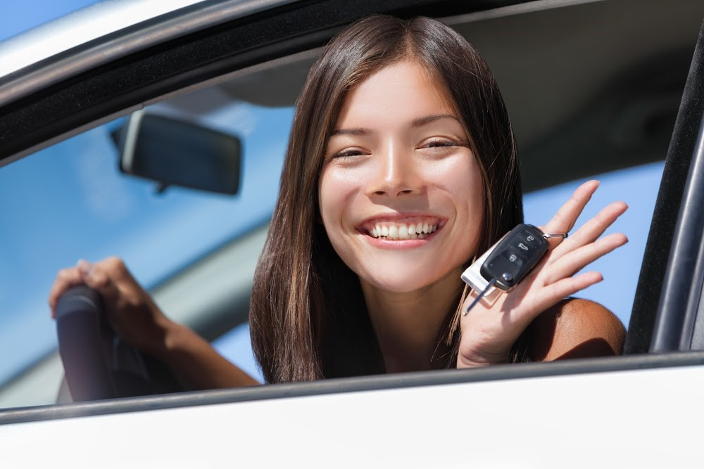Happy teen getting the keys for her car