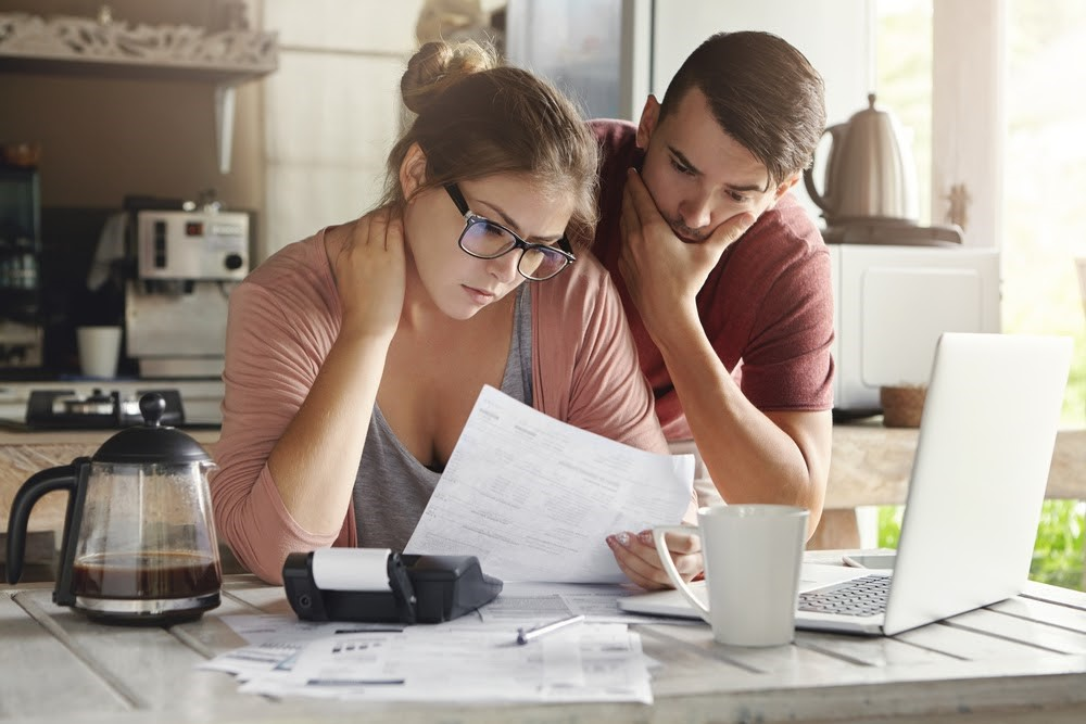 A couple reviewing their budget and stressing over money