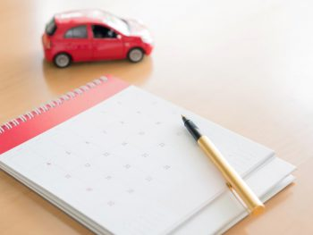 calendar with a gold pen sitting on a desk with a red toy car