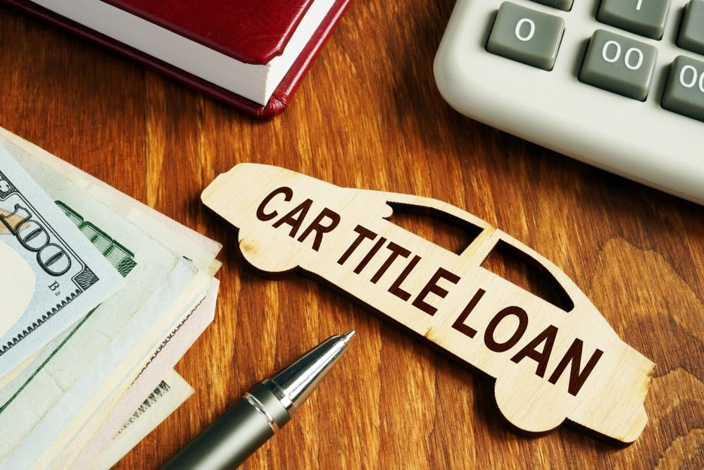 Money next to a calculator and a small wood car labeled 'car title loan