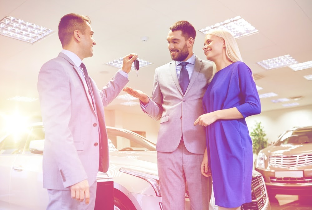 smiling couple accepting the keys from a car salesman in a dealership