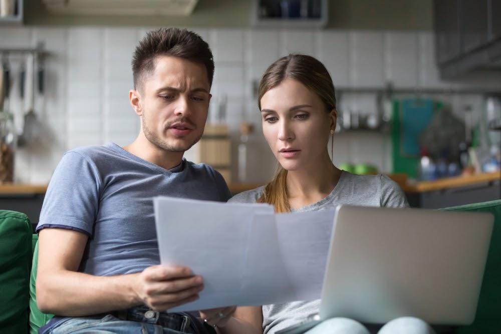 A couple reviews their finances on a computer spreadsheet.